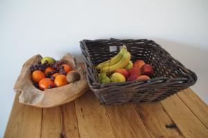 teak fruitschaal en rieten mand met fruit